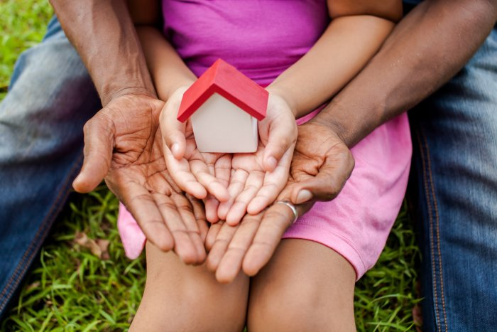 Child sitting on adults lap, both holding out hands carrying a model house